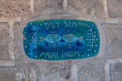 Un segno con il nome della via nell'ebreo - vicolo del segno dei pesci dello zodiaco dentro sulla vecchia città Yafo in telefono  Fotografia Stock