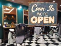 Un segno d'annata di affari che dice il ` entra noi ` con riferimento a ` aperto sul barbiere immagine stock