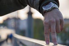 Un segno della mano dell'uomo sul fondo vago della città Due dita sulla superficie come la gamba della gente Immagine Stock