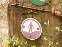 Un segno di camminata su una posta con un uomo in un cerchio Fotografia Stock