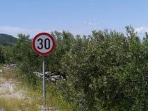 Un segno di limite di velocità di 30 chilometri e dei cespugli verde oliva Fotografia Stock