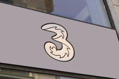 un segno di 3 logo sulla lastra di vetro del negozio 3 sono una marca commerciale globale nell'ambito di cui parecchie reti del t Fotografia Stock