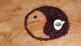 Un segno di yin e dell'yang dai chicchi di caffè Il segno di yang e del yin è presentato sulla tavola del marmo della cucina video d archivio