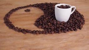Un segno di yin e dell'yang dai chicchi di caffè Il segno di yang e del yin è presentato sulla tavola del marmo della cucina Nel  video d archivio