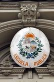 Un segno su una ' public school ' con la stemma uruguaiana Immagine Stock