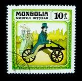 Un sello impreso en Mongolia muestra una imagen del hombre de A con una bicicleta corriente rodada dos del ` de la máquina del ` Imagen de archivo libre de regalías