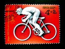 Un sello impreso en Rusia muestra una imagen de un hombre que completa un ciclo en la bici del camino para los juegos an o 80 de  Imágenes de archivo libres de regalías