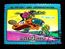 Un sello impreso en Rusia muestra una imagen de la historieta del lobo en el coche y el conejo de competición anaranjado que mont Fotos de archivo
