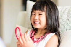 Un sembler asiatique de petite fille confortable quand docteur examinant par u images stock