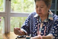Un senoir plus ancien mangeant du gâteau au fromage de myrtille au café Personnes âgées asiatiques Images stock