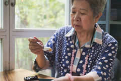 Un senoir plus ancien mangeant du gâteau au fromage de myrtille au café Personnes âgées asiatiques Images libres de droits