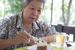 Un senoir plus ancien mangeant le gâteau de mousse de chocolat au café Femme âgée Photo stock
