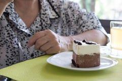Un senoir plus ancien mangeant le gâteau de mousse de chocolat au café Femme âgée Photographie stock libre de droits