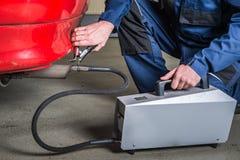 Un sensor de diagnóstico es aplicado al ehaust de un coche por un mecánico, midiendo la composición y las sustancias en Fotografía de archivo libre de regalías