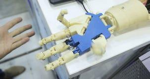 Un ser humano y manos biónicas que mienten al lado de uno a Brazo cibernético del robot, que controla a la gente metrajes