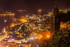 Un sera tardi sulla baia di Cattaro, una vecchia città si è acceso da luce arancio fotografie stock libere da diritti