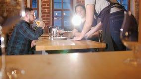 Un serveur donne un menu aux clients banque de vidéos