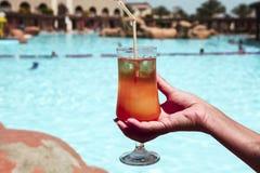 Un sesso alcolico delizioso del cocktail sulla spiaggia in una mano femminile sui precedenti dello stagno immagine stock