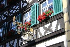 Un signe avec une lanterne sur une parenthèse et des fleurs en métal dans les fenêtres photos libres de droits