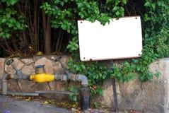 Un signe blanc devant un vert Photographie stock libre de droits