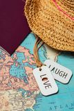 Un signe d'amour et un rire signent à côté d'un chapeau et d'un passeport sur heure du matin Photo stock