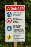 Un signe de danger avec la diverse plage ordonne là-dessus Photo libre de droits