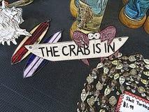 Un signe en forme de crabe lunatique lit le crabe est dedans parmi des tortues de coquille et des planches de surf en verre souil Photo stock