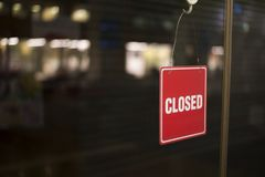 Un signe fermé accrochant de l'intérieur d'une porte en verre images libres de droits