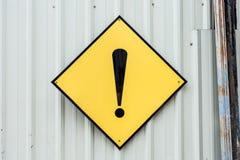 Un signe jaune en métal de marque d'exclamation de précaution Photo stock