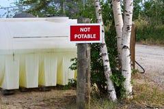 Un signe non potable à côté d'un réservoir de retenue d'eau Images libres de droits