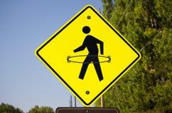 Un signe piétonnier jaune de passage piéton avec un cercle de danse polynésienne dessiné sur lui Photographie stock libre de droits