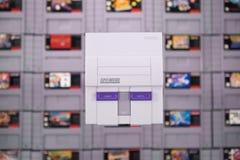 Un sistema clásico de Nintendo SNES que flota sobre cartuchos de SNES imagenes de archivo