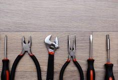 Un sistema con la herramienta en una tabla de madera Martillo, destornillador, llaves del gayachnye, alicates, cortaalambres Visi Foto de archivo