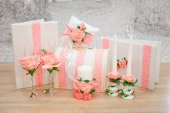 Un sistema de accesorios de la boda, adornado en cintas y joyería coloreadas Foto de archivo