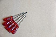 Un sistema de buceadores rojos del tornillo en un fondo de madera Fotos de archivo libres de regalías