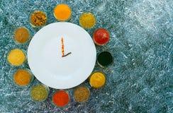 Un sistema de especias y las salsas se presentan alrededor de una placa vacía blanca bajo la forma de reloj Pimienta, sal, paprik imagen de archivo
