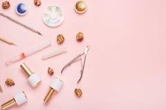 Un sistema de las herramientas cosméticas para la manicura y la pedicura en un fondo rosado Pulimentos del gel, ficheros de clavo foto de archivo