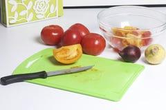 Un sistema de las verduras para la ensalada miente cerca de la tabla de cortar Cuchillo para cortar y un envase para la ensalada Fotografía de archivo libre de regalías