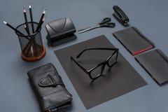 Un sistema de los accesorios negros de la oficina, vidrios en fondo gris Imágenes de archivo libres de regalías