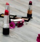 Un sistema de los cosméticos decorativos para el maquillaje y de las flores en un fondo blanco Opinión superior de los accesorios Fotografía de archivo