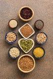 Un sistema de los diversos superfoods, granos enteros, habas, semillas, legumbres en cuencos en un fondo marrón de piedra Visión  foto de archivo