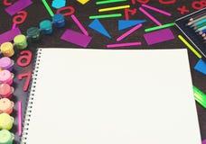 Un sistema de los efectos de escritorio para el cuaderno de la escuela que miente en la tabla Copia de la visión superior del con imagen de archivo
