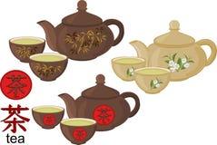 Un sistema de tazas de té y de tetera en un fondo blanco Foto de archivo libre de regalías