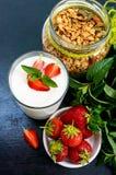 Un sistema de un producto para un desayuno sano delicioso: granola, yogur, fresas frescas Foto de archivo libre de regalías