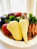 Un sistema de verduras naturales en un disco Pimienta, zanahorias, patatas, verdes, berenjena, cebolla, ajo Fondo blanco imagen de archivo libre de regalías