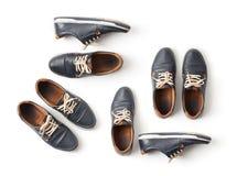 Un sistema de zapatos azules idénticos del ` s de los hombres en blanco Imagenes de archivo