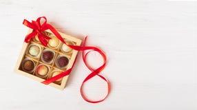 Un sistema del regalo de diversos caramelos en una caja que hace a mano se adorna con una cinta de satén roja Concepto festivo Di imagenes de archivo