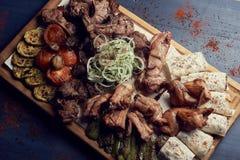 Un sistema grande de carne asada a la parrilla con las verduras en Platón de madera grande o la tabla de cortar en fondo de mader fotos de archivo libres de regalías