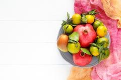 Un sistema hermoso de las frutas granada, mandarina, pera en la materia textil rosada e imagen horizontal del fondo de madera bla Fotos de archivo libres de regalías