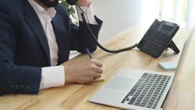 Un sittingin heureux d'homme d'affaires son bureau fonctionnant à son ordinateur banque de vidéos